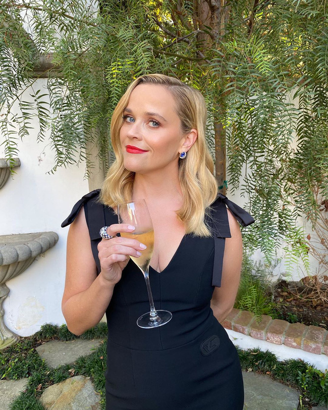 Reese Witherspoon lên đồ sang chảnh, tay cầm ly champagne.